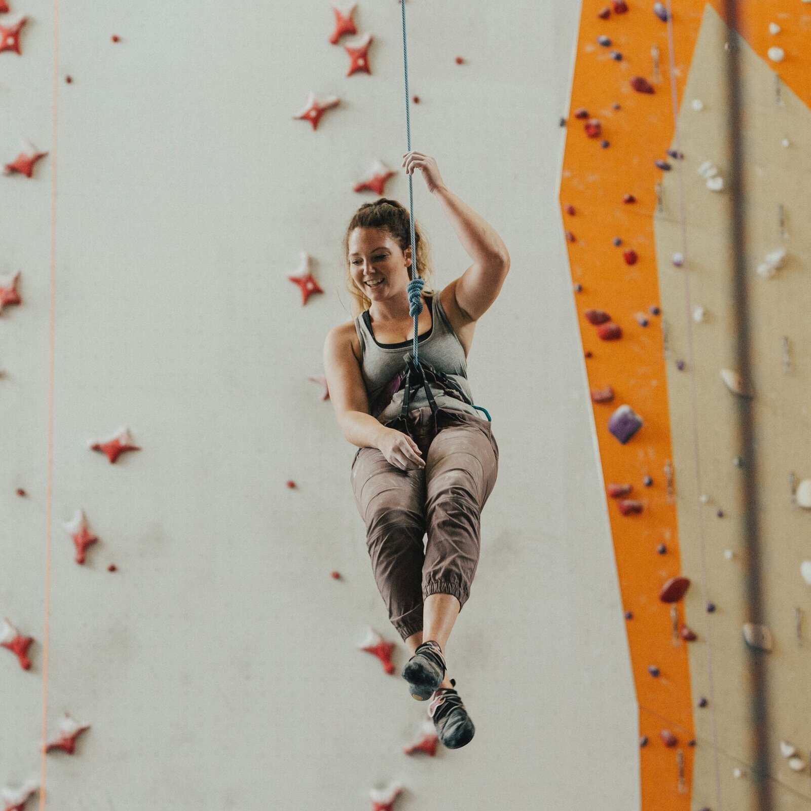 person going down rock climbing wall